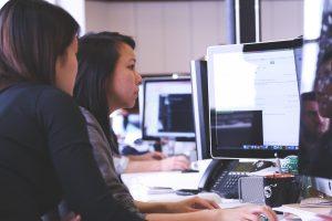 Dos noies en procés de formació, aprenent davant d'un ordinador.